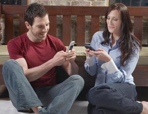 Couple Text Messaging on Floorの写真素材 [FYI02943143]