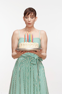 Woman blowing candles on birthday cakeの写真素材 [FYI02943144]