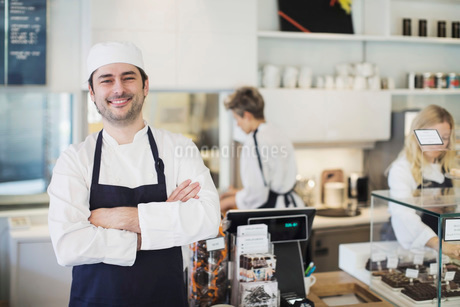 Portrait of confident owner standing arms crossed in cafeの写真素材 [FYI02943165]