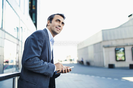 Confident businessman looking away while using mobile phone on sidewalkの写真素材 [FYI02943173]