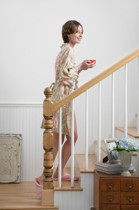Woman with tea cup walking up stairsの写真素材 [FYI02943225]