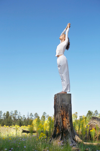 Young woman practicing yoga on stumpの写真素材 [FYI02943229]