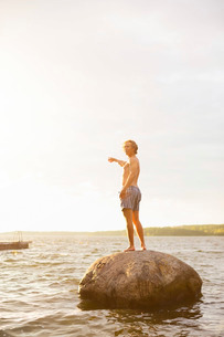 Full length side view of man pointing while standing on rock in lake against skyの写真素材 [FYI02943260]