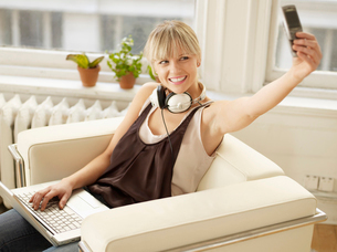 Woman Picture Messaging and Using Laptopの写真素材 [FYI02943372]