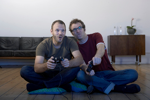 Two mid adult men playing video gamesの写真素材 [FYI02943425]