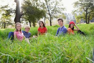 Five teenagers sitting in fieldの写真素材 [FYI02943428]