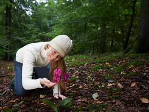 Woman Looking at Orchid in Forestの写真素材 [FYI02943429]