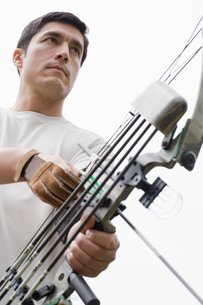 Man with bow and arrow (low angle view)の写真素材 [FYI02943432]
