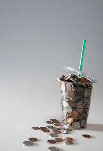 Coins Spilling from Disposable Cupの写真素材 [FYI02943436]
