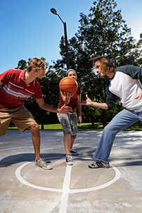 Three people playing basketballの写真素材 [FYI02943464]