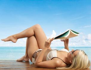 Young Woman in Bikini Reading Bookの写真素材 [FYI02943467]