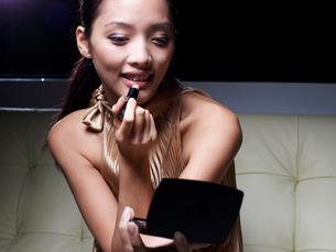 Mid-Adult Woman Applying Lipstickの写真素材 [FYI02943485]