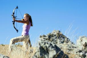 Young woman arrow shooting in fieldの写真素材 [FYI02943517]