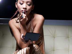 Mid-Adult Woman Applying Lipstickの写真素材 [FYI02943541]