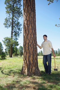Young man with axe standing by treeの写真素材 [FYI02943556]