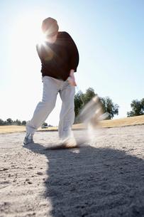 Man swinging golf club on sandの写真素材 [FYI02943560]