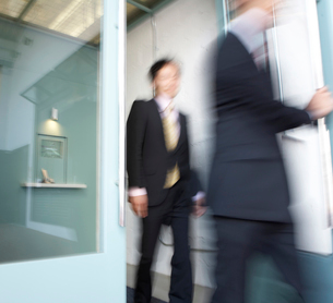 Two Businesspeople Walking Through Doorの写真素材 [FYI02943577]