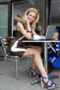 Mother with laptop talking on phoneの写真素材 [FYI02943689]