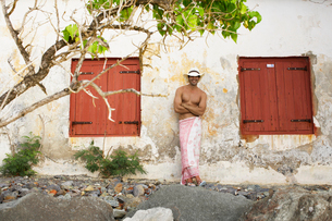 Young man in sarong and hat by old houseの写真素材 [FYI02943691]