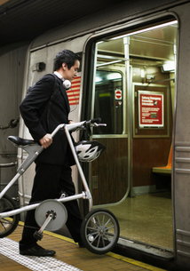 Businessman with Bicycle Boarding Subway Trainの写真素材 [FYI02943706]