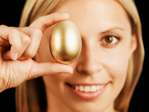 Woman Holding Golden Egg on Her Eyeの写真素材 [FYI02943721]