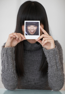 Mid-Adult Woman Holding Photograph of Herselfの写真素材 [FYI02943736]
