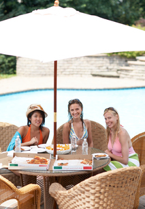 Three Female Friends Eating by Poolの写真素材 [FYI02943746]