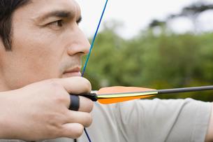 Mid adult man arrow shooting (close-up)の写真素材 [FYI02943753]