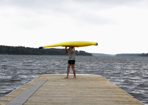 Woman Carrying Kayak on Her Headの写真素材 [FYI02943760]