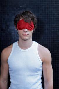 Young man wearing sleep maskの写真素材 [FYI02943785]