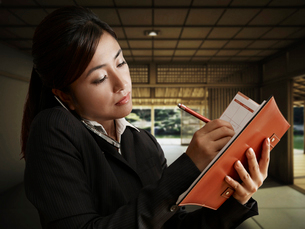 Businesswoman Writing on Diary While on Phoneの写真素材 [FYI02943815]