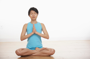 Mid Adult Woman Meditating in Lotus Positionの写真素材 [FYI02943838]
