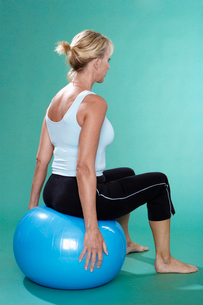 Mature woman exercising on Swiss ballの写真素材 [FYI02943865]