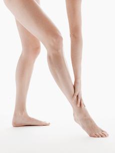 Young woman touching her legの写真素材 [FYI02943868]