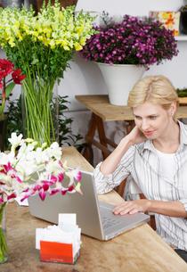 Female florist using laptopの写真素材 [FYI02943888]