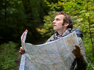 Male Hiker Reading Map in Forestの写真素材 [FYI02943939]