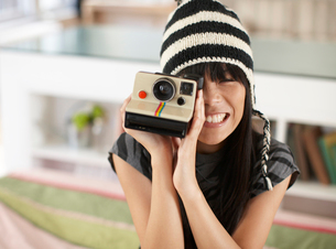 Mid Adult Woman Using Instant Cameraの写真素材 [FYI02943962]