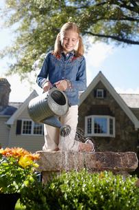 Girl watering flowersの写真素材 [FYI02943986]