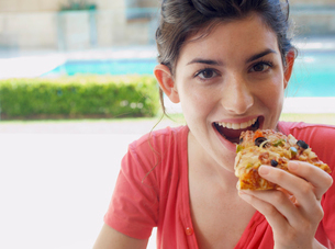 Young woman eating pizzaの写真素材 [FYI02943993]