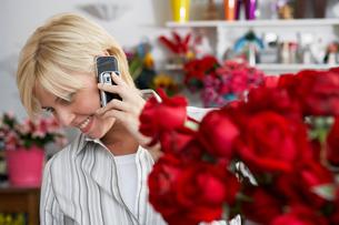 Female florist on cell phoneの写真素材 [FYI02944021]