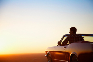 Man looking at sunset in convertibleの写真素材 [FYI02944027]
