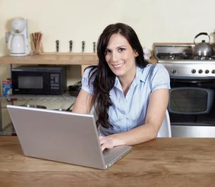 Woman Using Laptop in Kitchenの写真素材 [FYI02944077]