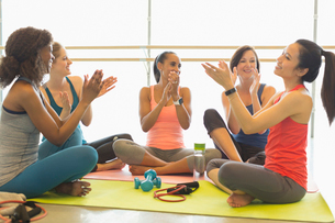 Smiling women clapping in gym studioの写真素材 [FYI02944109]