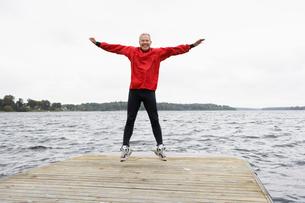 Senior man jumping on jettyの写真素材 [FYI02944119]