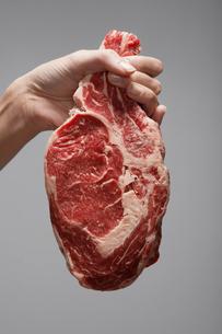 Womans hand holding raw steakの写真素材 [FYI02944292]