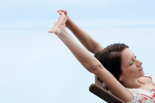 Young woman stretching on lounge chairの写真素材 [FYI02944313]