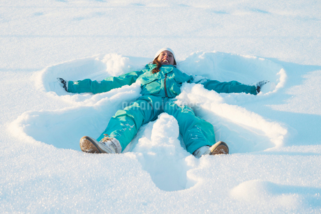 Sweden, Jamtland, Are, Woman making snow angelの写真素材 [FYI02944316]
