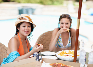 Two Mid-Adult Women Eating by Poolの写真素材 [FYI02944333]