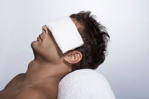 Mid adult man lying with towel over eyesの写真素材 [FYI02944336]