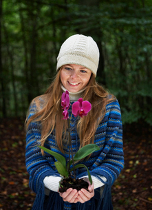 Mid Adult Woman Holding Orchid in Forestの写真素材 [FYI02944353]
